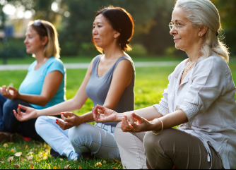 Three women outdoors in seated yoga poses to illustrate benefits of Phreesia's Women's Wellness for OB/GYN application