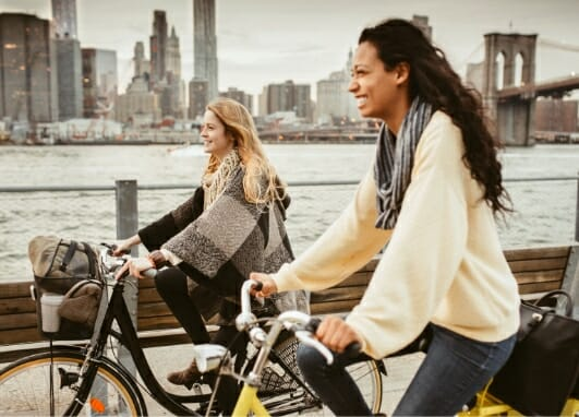 Two women riding bikes to illustrate benefits of Phreesia's Care Pathways for Dermatology application