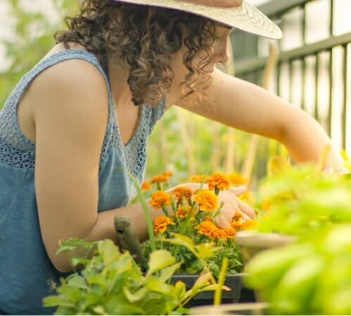 Woman outdoors tending to her flower garden to illustrate benefits of Phreesia's Care Pathways for ENT application