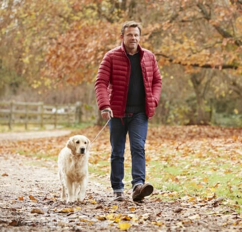 Man out walking on his dog to illustrate benefits of Phreesia's Care Pathways for Neuro, Pain and Spine application