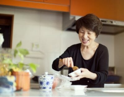 Woman smiling and cooking in her kitchen to illustrate benefits of Phreesia's Care Pathways for Rheumatology application