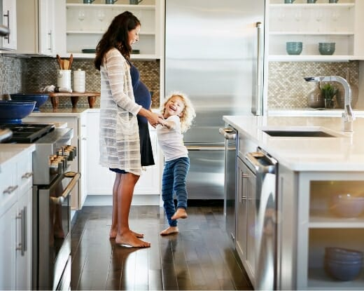 Pregnant mother with her daughter, dancing in the kitchen, to illustrate benefits of Phreesia's Healthy Child for Pediatrics application