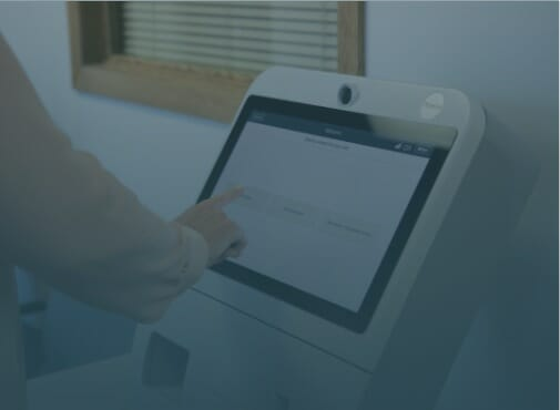 Video thumbnail image of a patient interacting with the Phreesia Arrivals station kiosk