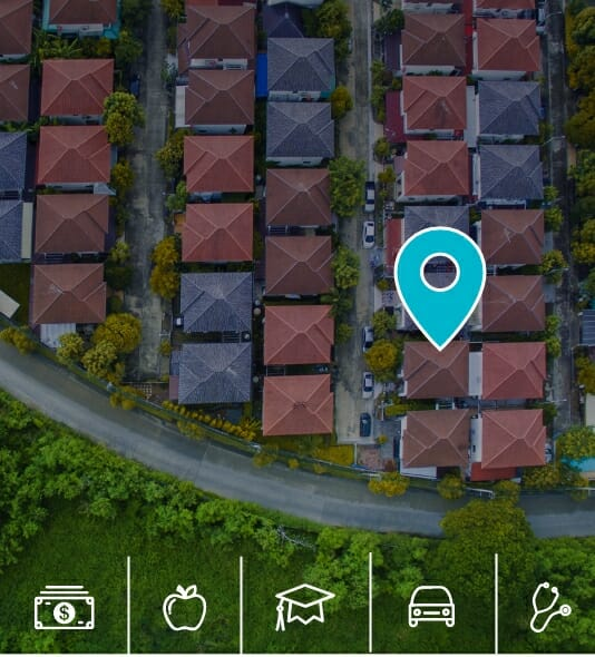 Aerial view of a cluster of neighborhood rooftops with a location marker icon to illustrate importance of Social Determinants of Health.