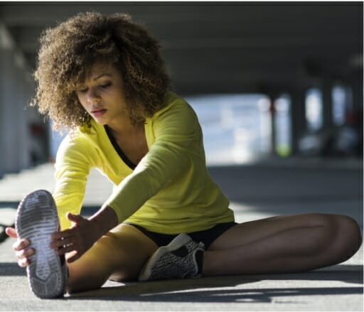 Woman doing stretching exercises in a gym to demonstrate benefits of Phreesia's Wellness for health systems app